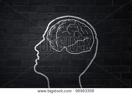 Human hand drawing brain on black chalkboard