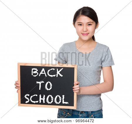 Young woman with the blackboard and showing phrase of back to school