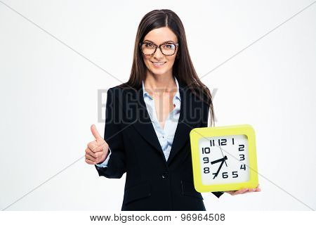 Smiling businesswoman holding clock and showing thumb up isolated on a white background