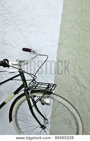 Detail of a vintage green and yellow bicycle against a wall