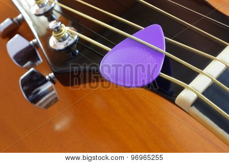 Closeup of a purple pick on metallic chord in acoustic guitar head stock