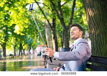 Cheerful businessman making selfie photo on smartphone outdoors