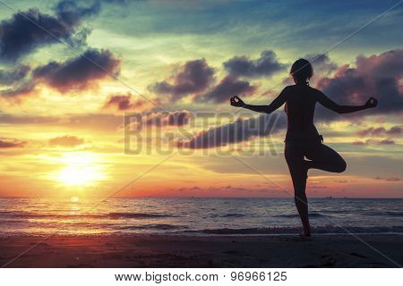 Silhouette of woman standing at yoga pose on the ocean beach during an fantastic sunset.