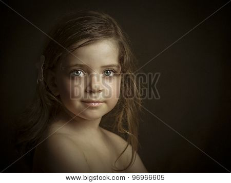 Little girl with blue eyes and blond hair in studio.