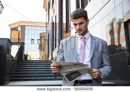 Portrait of a handsome businessman reading newspaper outdoors