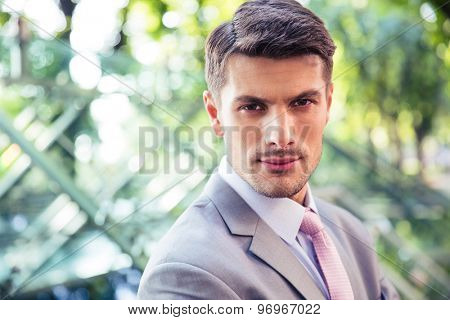 Portrait of a handsome businessman outdoors looking at camera