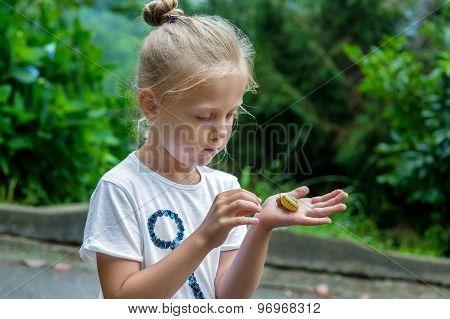 Little Girl Holding Snail In Hand