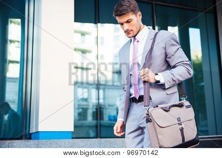 Confident businessman walking outdoors near office building