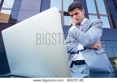 Portrait of a worried businessman looking at laptop outdoors