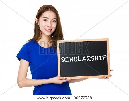 Student hold with wooden chalkboard showing a word scholarship