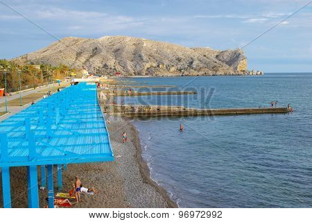 SUDAK, CRIMEA, UKRAINE - SEPTEMBER 22, 2006: People resting on the public beach. It the only town in Crimea, which has beaches of quartz sand