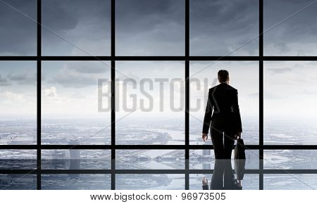 Businesswoman standing with back and looking in office window