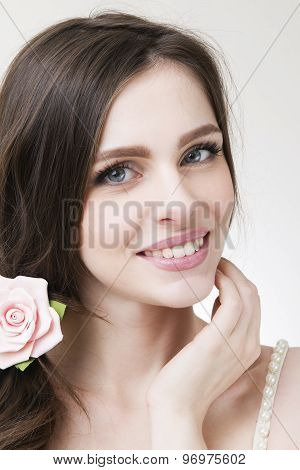 Studio Portrait Of A Young Beautiful Bride. Professional Make-up And Hairstyle With Flowers