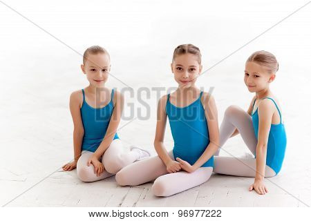 Three little ballet girls sitting and posing together