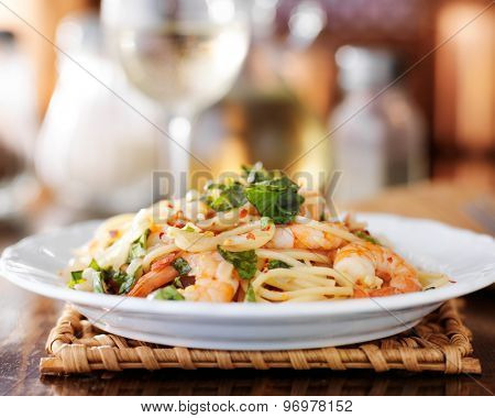 eye level view of shrimp spaghetti pasta on a white plate and white wine in background