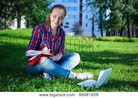 Teenage Girl Writing Diary In Park