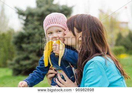 Mom Kisses The Girl Who Eats A Banana On Picnic