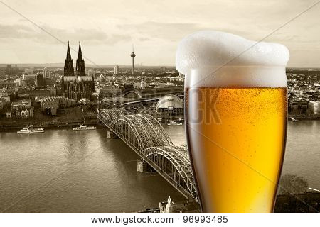 Glass of beer with view of Koln on background, Germany