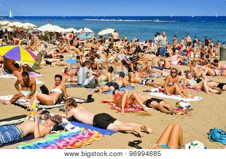 BARCELONA, SPAIN - AUGUST 19: A crowd of bathers in La Barceloneta Beach on August 19, 2014 in Barcelona, Spain. This popular beach hosts about 500000 visitors from everywhere during the summer season