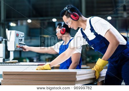 Two wood workers in carpentry cutting boards putting them in saw