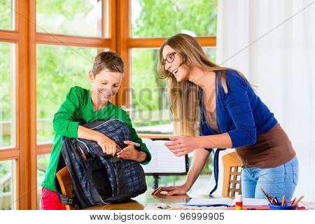 Mother and son packing school bag for next day
