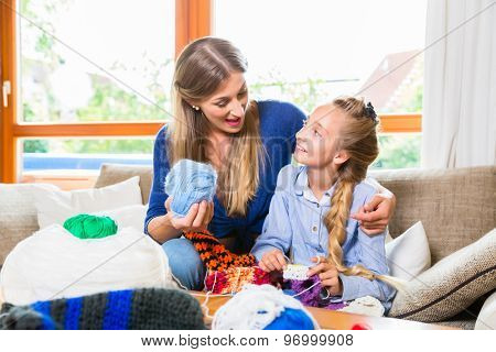 Mother teaching daughter knitting
