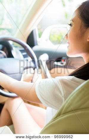 Asian woman driving new car