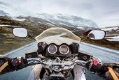 picture of slippery-roads  - Biker rides a motorcycle on a slippery road through a mountain pass in Norway - JPG