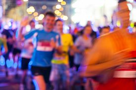 foto of competing  - Blurred Marathon running race people competing in fitness and healthy active lifestyle feet on road. ** Note: Visible grain at 100%, best at smaller sizes - JPG