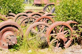 picture of train-wheel  - A stockpile of old rusty and abandoned train wheels lying in the grass close to train service depot - JPG