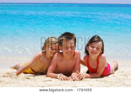 Happy Children Laying On Beach