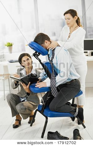 Occupied executive continue working while getting back massage in office.?