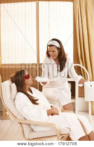 Beautician preparing for cosmetic laser tooth whitening treatment at beauty saloon.?