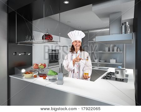 Smiling female chef behind a modern kitchen counter pointing at a bottle of olive oil