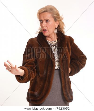 Portrait of a horrified elegant senior lady in a mink coat with a stopping hand