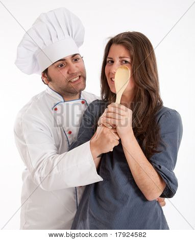A professional chef and a young woman fighting for the possession of a wooden spoon