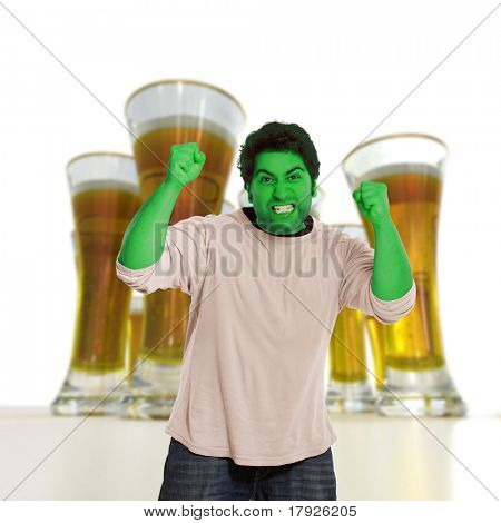 Green young man in a fit of rage with beers on the background