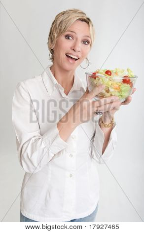 Short haired blond woman holding a salad bowl