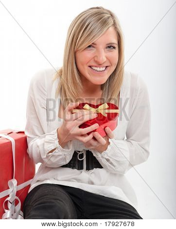Cute young woman greatly surprised with a heart shaped box
