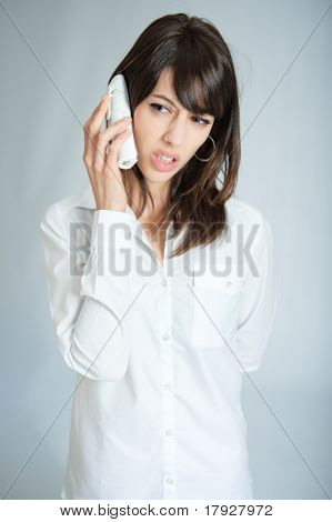 Young brunette talking on the phone with an annoyed expression