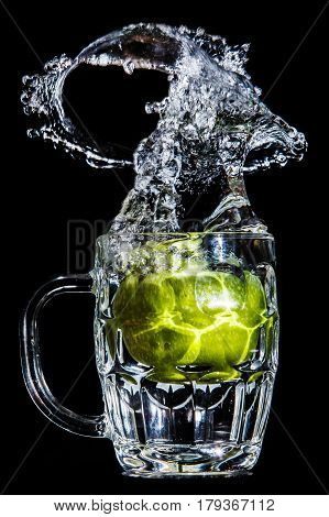 Artistic splash of a green apple created after being dropped into a clear goblet.