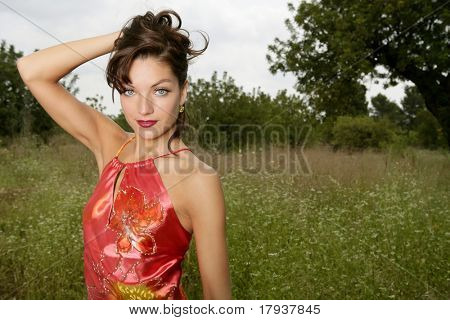 woman elegant, with red dress haute couture, on the forest outdoors
