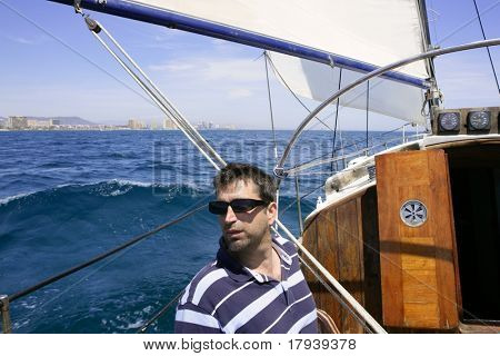 Sailor sailing blue tropical sea on sailboat in summer vacation