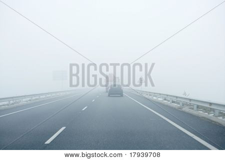 Foggy gray road, cars driving vanish into the fog