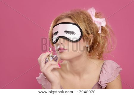 blond woman smelling perfume sleep mask blind pink background