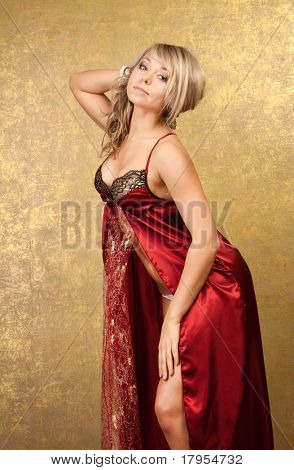 sexy blonde woman in red seductive dress on golden background