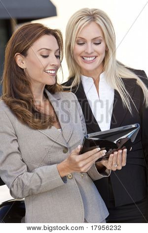 Two happy and smart businesswomen using a tablet computer