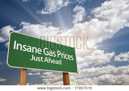 Insane Gas Prices Green Road Sign with Dramatic Clouds, Sun Rays and Sky.