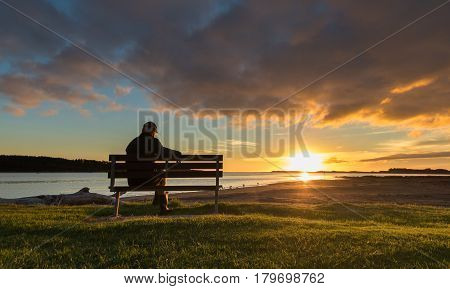 A man on a seat watching the sunset at Foxton Beach river.