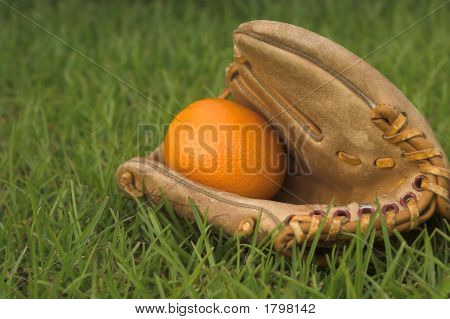 An Orange In A Baseball Glove